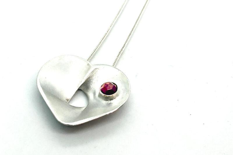 Hõbedast südamekujuline kaelaehe kiviga, vääriskivi punane granaat. Süda 400mm, kett 700mm. Eesti disain.