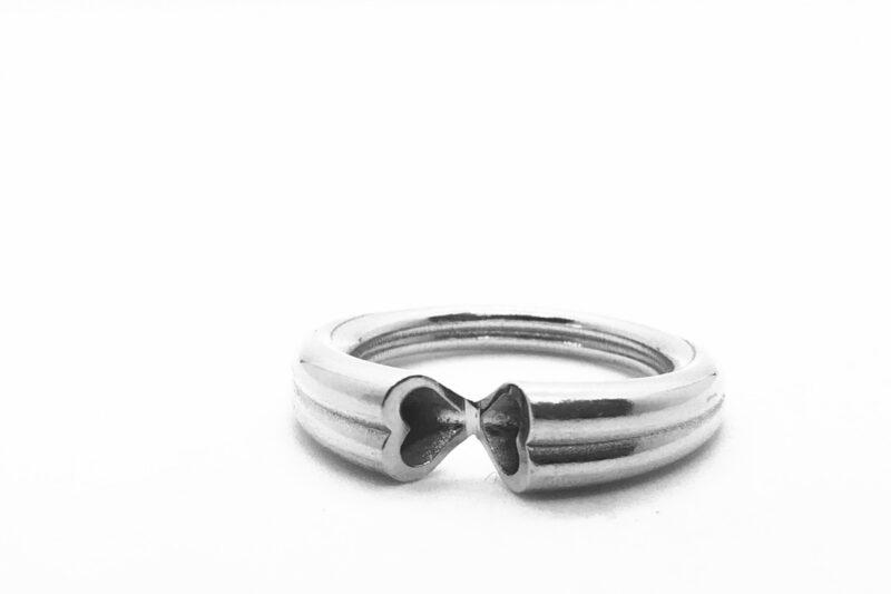 Kolme soonega hõbedane sõrmus mille ühenduskohas on mõlemal pool südame motiiv.